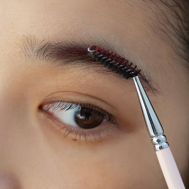 【ノーズシャドウの入れ方】3.スクリューブラシに取ったBは、眉頭を外し毛流れに逆らってとかしつけ、さらに、毛流れに沿ってつける。
